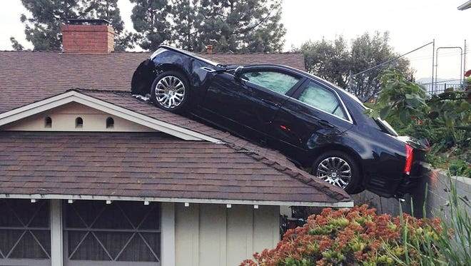 "A black Cadillac that lost control and careened onto the roof of a neighbor's home on Saturday, March 23, 2013 in Glendale, Calif. The Cadillac driver lost control before leaving his driveway, plunging off a hill ""onto the roof of his neighbor's house directly below his driveway."