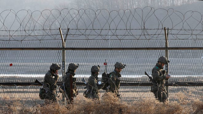 South Korean army soldiers patrol along a barbed-wire fence near the border village of Panmunjom in South Korea on March 26.