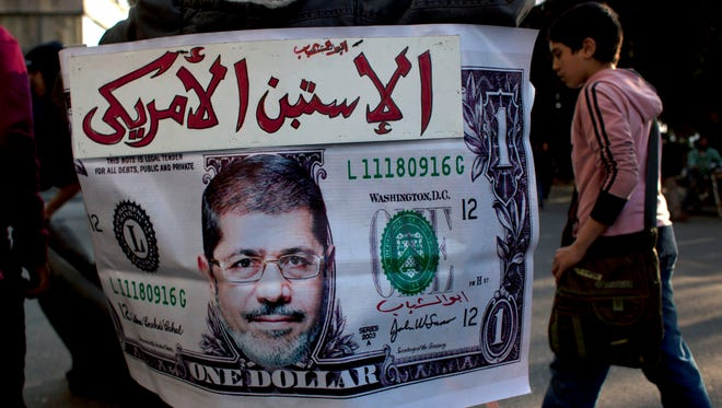 An Egyptian protester's placard depicts a U.S. dollar with a picture of President Mohammed Morsi on March 5 in Cairo. The Egyptian pound continues to fall against the U.S. dollar.