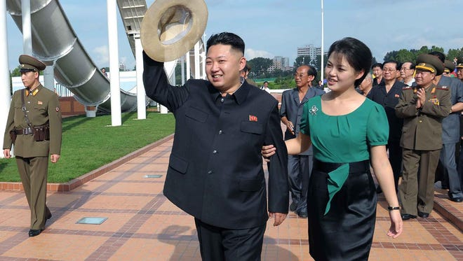 In this July 25, 2012 file photo released by the Korean Central News Agency (KCNA) and distributed in Tokyo by the Korea News Service, Kim Jong Un, accompanied by his wife Ri Sol Ju, waves to the crowd as they inspect the Rungna People's Pleasure Ground in Pyongyang.