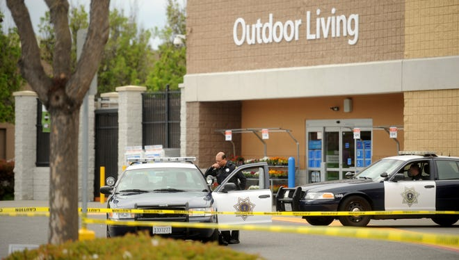 Police cars maintain a perimeter around a San Jose, Calif., Walmart after a motorist drove through a store entrance and began assaulting shoppers on March 31.