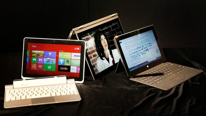 This photo taken Tuesday March 26, 2013 shows three hybrid computers running on Windows 8, from left to right, the Iconia W510 by Acer, the Yoga 13 by Lenovo and the Surface Pro by Microsoft, in Los Angeles.