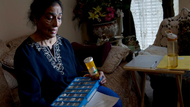 Amarjit Deol sits in her Cane Ridge, Tenn. home with her weekly medications and a letter from the Tennessee Board of Health. The letter outlines the symptoms she likely will continue to experience since she contracted fungal meningitis from tainted steroids at St. Thomas Hospital in September 2012.