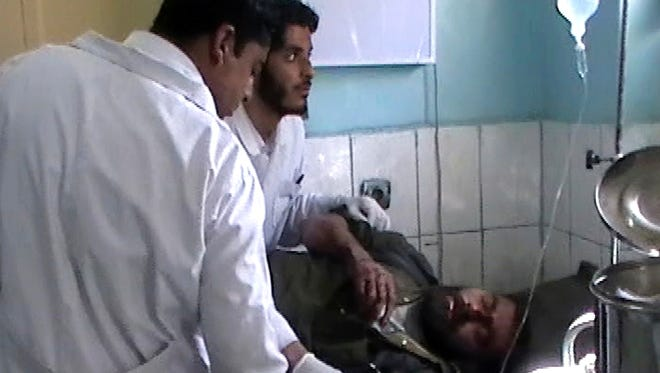 This image made from AP video shows doctors attending to an injured man at the local hospital in Farah, western Afghanistan on Wednesday.