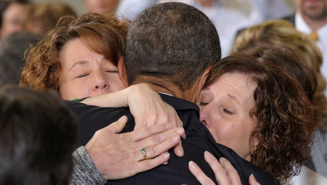 President Barack Obama embraces Jane Dougherty, sister of slain Sandy Hook Elementary School psychologist Mary Sherlach, right, and an unidentified woman after speaking at the Denver Police Academy in Denver on Wednesday.