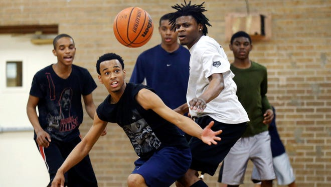 In this March 30, 2013, photo, Demaris Johnson, left, and Javon Reynolds, right, look for a loose ball during a basketball game during the Windy City Hoops program at the Kennicott Park recreation center in Chicago.