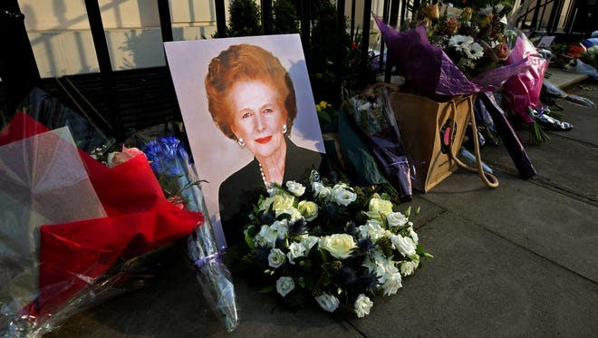 A portrait of former prime minister Margaret Thatcher is left next to floral tributes outside her residence in Chester Square on Monday in London.
