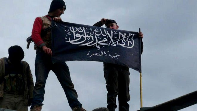 In this Jan. 11, 2013 file citizen journalism image provided by Edlib News Network, ENN, which has been authenticated based on its contents and other AP reporting, shows rebels from al-Qaida affiliated Jabhat al-Nusra waving their brigade flag on the top of a Syrian air force helicopter, at Taftanaz air base that was captured by the rebels, in Idlib province, northern Syria.