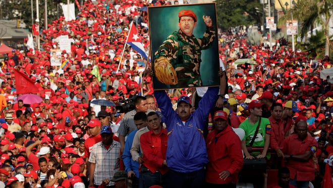 Venezuela's acting President Nicolas Maduro holds up a painting of late President Hugo Chavez during a campaign rally in Catia La Mar, Vargas state, Venezuela, Tuesday, April 9, 2013. Maduro, the hand-picked successor of late President Hugo Chavez, is running for president against opposition candidate Henrique Capriles on April 14. (AP Photo/Ariana Cubillos) ORG XMIT: XAC101
