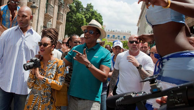 U.S. singer Beyonce and her husband, rapper Jay-Z, are surrounded by body guards as they tour Old Havana where a street performer on stilts looks on, right, in Cuba, Thursday, April 4, 2013.