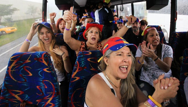 Arleth Garay, front, with, behind from left to right,  Mariana Garay, and  Marlene Garay,  board a bus at JC Bermundez park in Doral, Fla. on Saturday afternoon before leaving with thousands of South Florida Venezuelans on a 16 hour bus trip to New Orleans to vote in the Venezuelan presidential elections on Sunday.