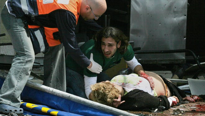A man holds on to a victim of a suicide bomb attack  near a fast-food restaurant in Tel Aviv on April 17, 2006.