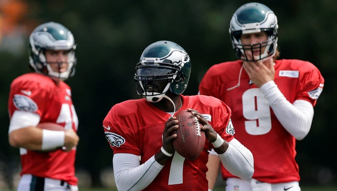 Eagles quarterback Michael Vick  drops back to pass as  Nick Foles (9) looks on during  practices at the team's facility in Philadelphia on Sept. 5, 2012.