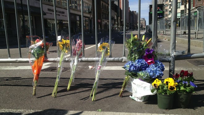 Flowers mark a makeshift memorial on the corner of Boylston and Arlington Streets on the edge of the security perimeter in Boston.