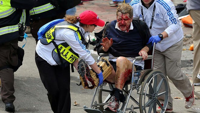 Medical workers aid an injured man at the 2013 Boston Marathon after the attacks Monday.
