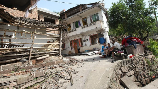 Residents rest outside damaged houses in Longmen township, an area near to the epicenter of magnitude-6.6 quake that hit the city of Ya'an, southwest China's Sichuan province on Saturday.