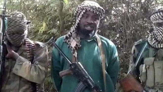 """A picture taken from a video distributed to Nigerian journalists in the country's north in recent days through intermediaries and obtained by AFP on March 5, 2013 reportedly shows Abubakar Shekau (C), the suspected leader of Nigerian Islamist extremist group Boko Haram, flanked by two armed and hooded fighters in an undisclosed place. The suspected leader of Nigerian Islamist group Boko Haram denies any ceasefire deal with the government in a video obtained today. Abubakar Shekau makes no mention of kidnappings in the video, including last month's abduction of seven members of a French family. Boko Haram was blamed for the kidnapping that occurred just over the Nigerian border in Cameroon. RESTRICTED TO EDITORIAL USE - MANDATORY CREDIT """"AFP PHOTO / BOKO HARAM"""" - NO MARKETING NO ADVERTISING CAMPAIGNS - DISTRIBUTED AS A SERVICE TO CLIENTSHO/AFP/Getty Images ORIG FILE ID: 517927981"""