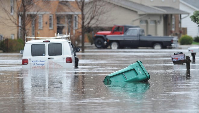 A garbage can floats past a disabled van on a street in Plainfield, Ill., on April 18, after torrential rains that began the day before caused widespread flooding.