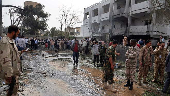 Security personnel inspect the site of a car bomb that targeted the French embassy in Tripoli, Libya, on April 23, 2013.