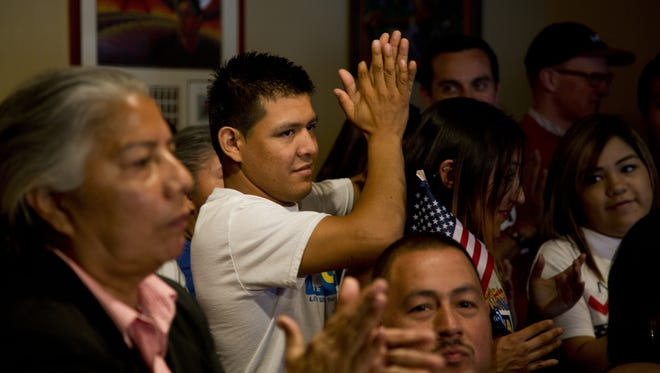 Raul Gallardo, center, applauds after an April 17 news conference in Phoenix, where Latino politicians commented on the immigration reform plan from the Gang of Eight. Many in Arizona believe the state may have a new role in immigration reform.