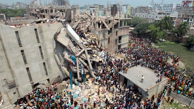 Rescuers and bystanders gather after an eight-story building housing several garment factories collapsed in Savar, near Dhaka, Bangladesh, on Wednesday.