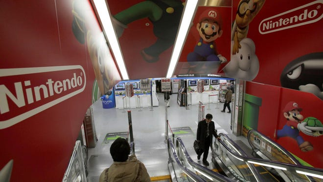 Shoppers take escalators under the logo of Nintendo and Super Mario characters at an electronics store in Tokyo, Wednesday, Jan. 30, 2013.
