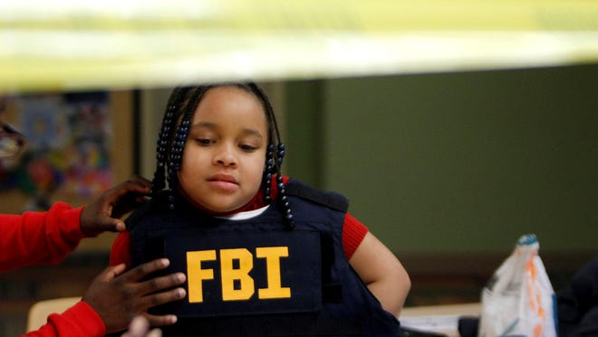Bella Jones, tries on a 30 pound FBI issued bullet proof vest during a Junior Special Agent training class at Ellen Thompson Elementary School in Detroit on Monday.
