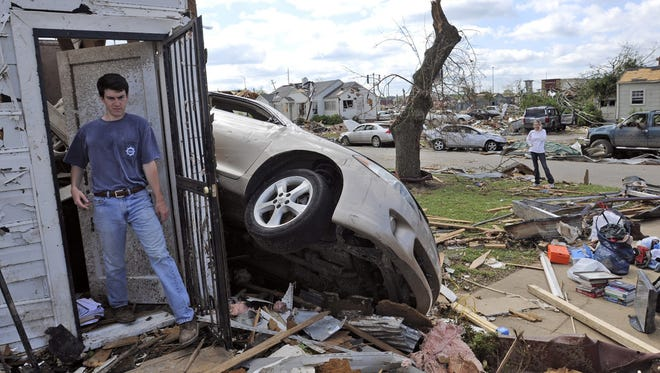 Daniel Hinton looks through the remains of his house on April 28, 2011, after a strong tornado ripped through Tuscaloosa, Ala.