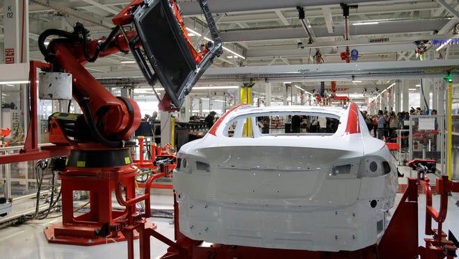 Robot installs roof on a Tesla Model S at Fremont, Calif., factory.