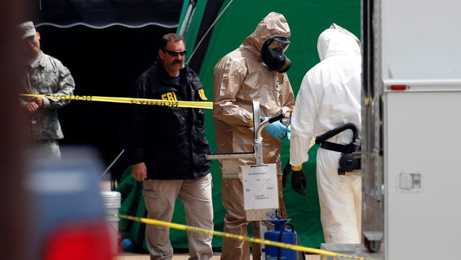 Federal authorities wear hazmat suits Wednesday during a search of a retail space in Tupelo, Miss., where neighboring business owners said Everett Dutschke used to operate a martial arts studio.