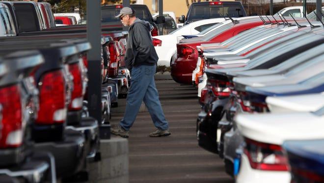 A car shopper walks between rows of 2013 Ram pickup trucks and Dart sedans at a Colorado Dodge dealership.