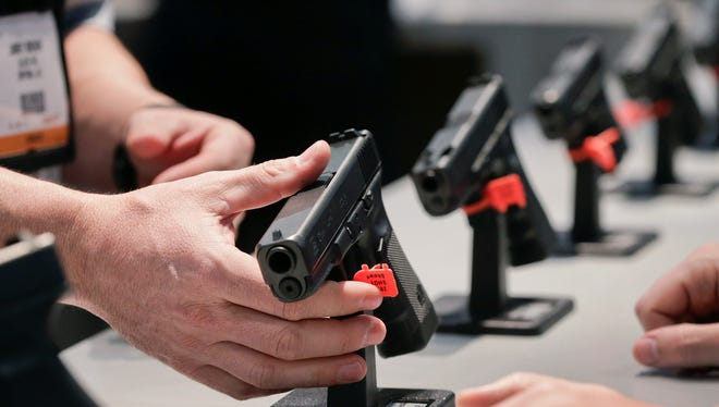 In this Jan. 16, 2013 file photo, a Glock representative explains features of the Glock 37 Gen 4 .45 caliber pistol at the 35th annual SHOT Show, in Las Vegas.