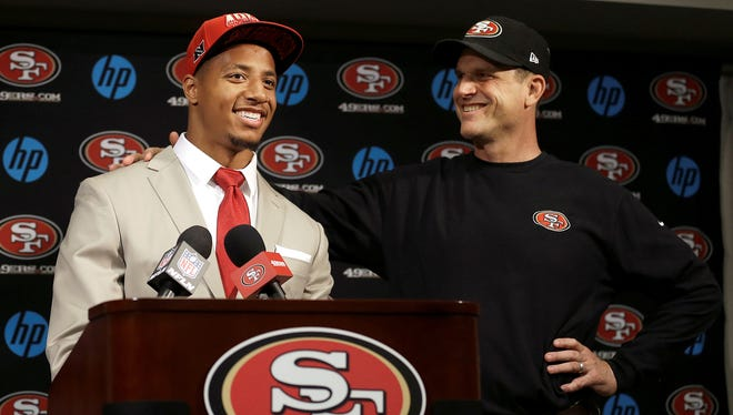Safety Eric Reid, the first-round draft pick of the San Francisco 49ers, left, smiles as he  stands next to  coach Jim Harbaugh during a news conference at the team's training facility in Santa Clara, Calif., Friday, April 26, 2013.