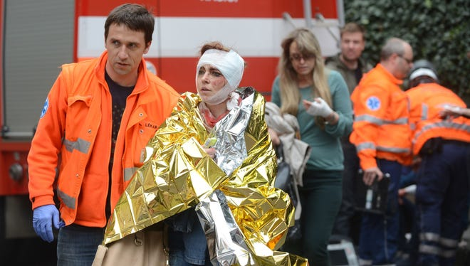 Rescue workers help a woman who was injured in a blast next to the building where an explosion happened on April 29 in Prague, Czech Republic.