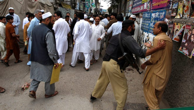 A Pakistani police officer pushes back people from the site of explosion in Peshawar, Pakistan, on April 29, 2013.