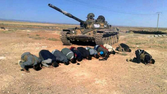 Syrian rebels pray in front their tank Tuesday at al Mutayia village, in the southern province of Daraa, Syria.