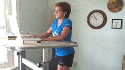 Janet Oberholtzer walks slowly while working. She can't sit for long periods after an injury from a serious car accident.