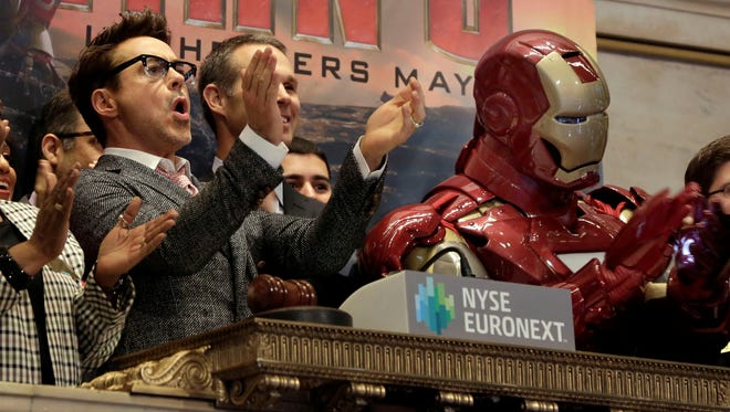 """Actor Robert Downey Jr. celebrates with his """"Iron Man"""" character during opening-bell ceremonies of the New York Stock Exchange on April 30, 2013."""