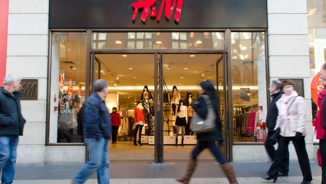 People walk by a branch of Swedish retail giant H&M in central London.
