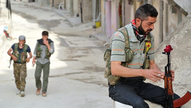 A rebel fighter of the Syrian Kurdish Popular Protection Units displays a flower in his Russian-made AK-47 Kalashnikov rifle as he holds a position in Aleppo on May 9.