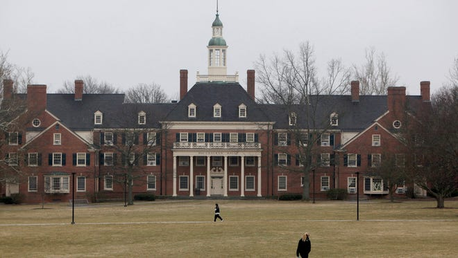 Students walk across the lawn in front of MacCracken Hall at Miami University, in Oxford, Ohio on March 5. College tuition keeps increasing, students keep borrowing - mainly from taxpayers - and universities keep spending.