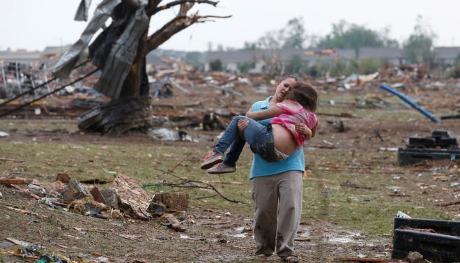 A woman carries her child through a field near the collapsed Plaza Towers Elementary School in Moore, Okla., on Monday.