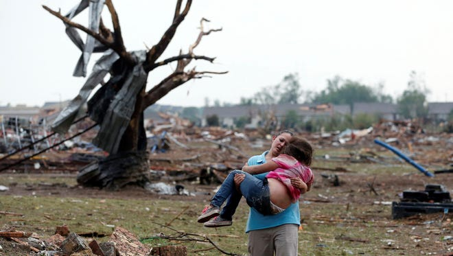 A woman carries her child through a field Monday near the collapsed Plaza Towers Elementary School in Moore, Okla.