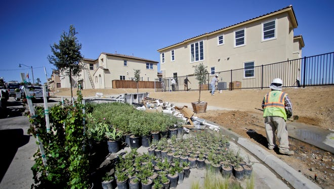 Finishing touches are being put on new homes under construction last month in Carlsbad, Calif.