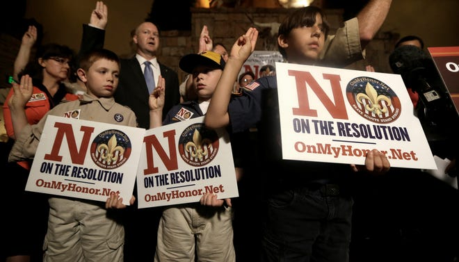 Boy Scouts from right, Joey Kalich, 10, Steven Grime, 7, and Jonathon Grime, 9, raise their hands at the close of a news conference held by people against the change in the Boy Scouts of America gay policy Wednesday, May 22, 2013, in Grapevine, Texas.