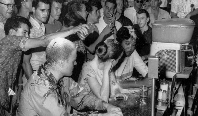 In this May 28, 1963, photograph, a group of whites pours sugar, ketchup and mustard over the heads of a multiracial group of Tougaloo College demonstrators during a sit-in at a Woolworth's lunch counter in Jackson, Miss. Seated at the counter, from left, are Tougaloo College professor John Salter and students Joan Trumpauer and Anne Moody.