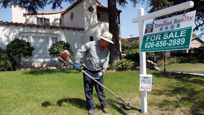 Gardener Jose Lopez trims the front lawn of a home for sale in Alhambra, Calif.  Mortgage rates have been creeping up in recent weeks.
