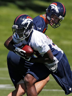 Denver Broncos quarterback Peyton Manning hands the football off to running back Montee Ball during offseason practices in Englewood, Colo., on Thursday, May 30, 2013.