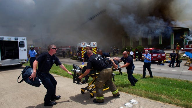 A firefighter is wheeled to an ambulance after fighting a fire at the Southwest Inn, Friday.