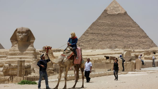 A tourist takes a camel ride at the pyramids May 31  in Cairo.